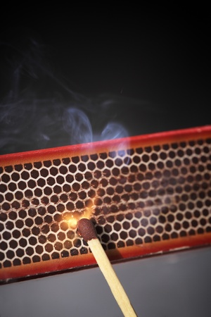 Striking a match against a match box. Stock Photo