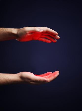 glows: Hands of a man with a red glow. Stock Photo