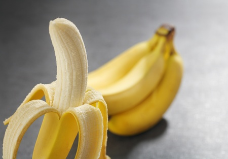 peeled banana: One peeled banana and a bunch of bananas in the background. Stock Photo
