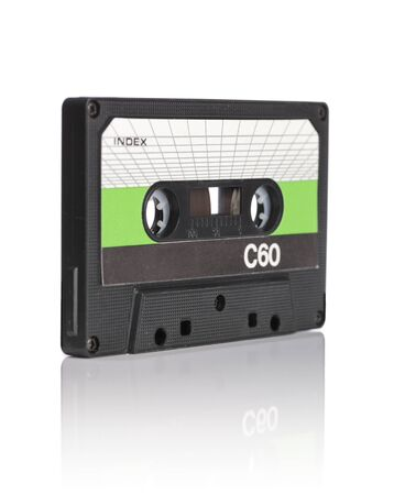 Old compact audio cassette on reflective white background. Very short depth-of-field. Stock Photo - 12247584