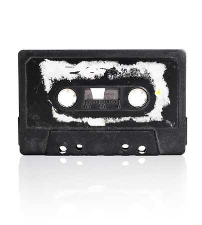 audio cassette: Old black compact audio cassette with torn label isolated on white with natural reflection.