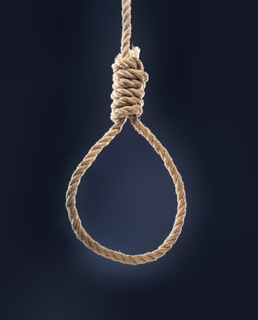 capital punishment: Rope noose with hangmans knot hanging in front of blue background.