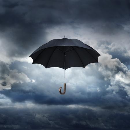 lluvia paraguas: Viejo paraguas negro contra el cielo lluvioso.