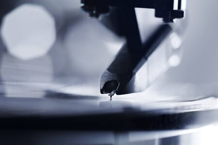 Closeup of a turntable stylus playing on a vinyl LP record. photo