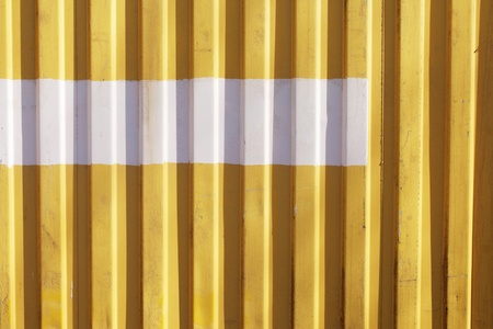 Detail of old yellow metallic cargo container with a partial  white stripe.