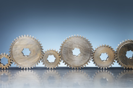 Old steel cog wheels on reflective background.