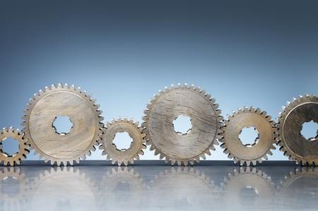reflective background: Old steel cog wheels on reflective background.