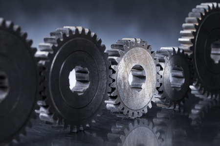 Old worn metallic cog gear wheels, with one gear in spotlight. Stock Photo