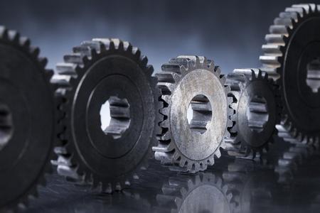 Old worn metallic cog gear wheels, with one gear in spotlight. Stockfoto