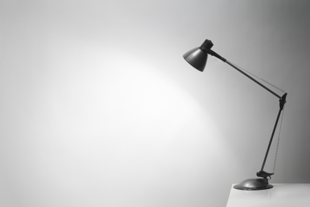 An office desk lamp illuminating the background. Lots of copy space. photo