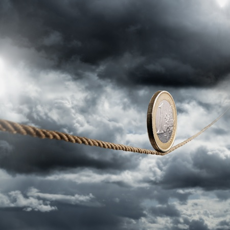 Euro coin balancing on a tightrope.
