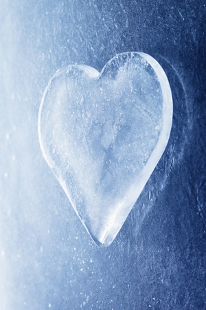 A Heart-shaped piece of ice on ice background. photo