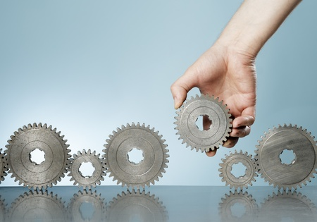 Man adding a cog gear in a row of old cog gears.