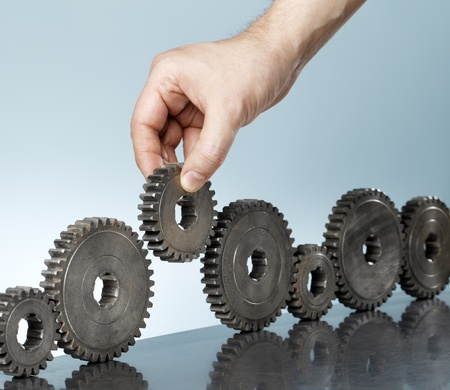 filling: Man adding a cog gear in a row of old cog gears.