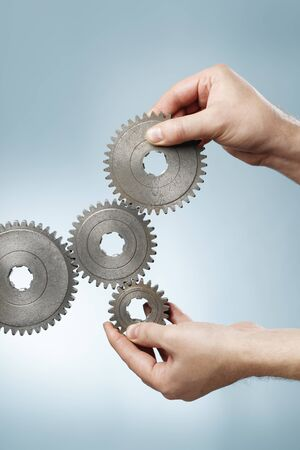 toothed: Man designing a mechanic system with old metallic cog gear wheels.