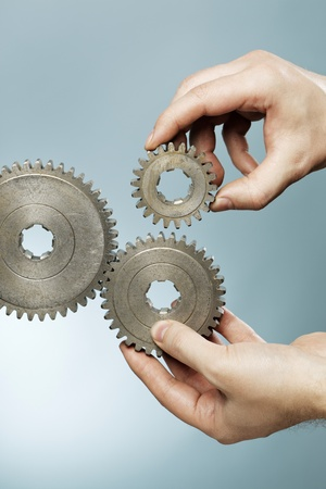 coupling: Man designing a mechanical system using old cog gear wheels.
