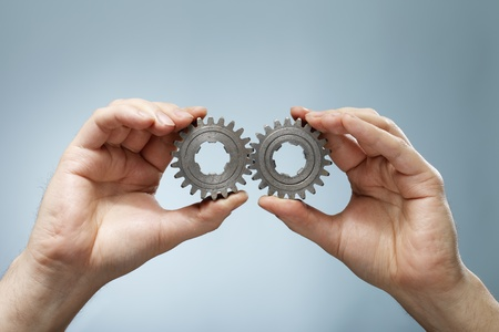 matching: Un hombre con un par coincidente de las antiguas ruedas dentadas de engranajes en sus manos. Foto de archivo