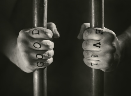 gripping bars: Man with (fake) Good and Evil tattoos behind prison bars.