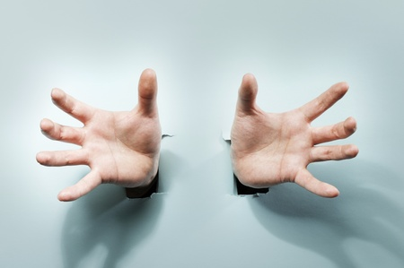 grabbing hand: Strange hands coming through holes in a blue cardboard. Stock Photo