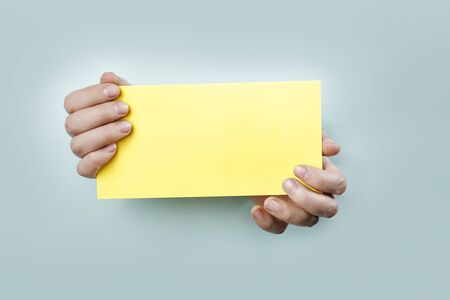 Strange hands holding a yellow card. Stock Photo - 12956175