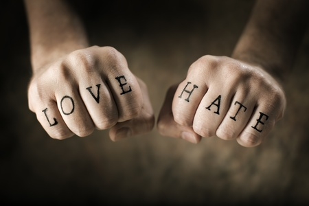 clenched: Man with (fake) Love and Hate tattoos on his hands.