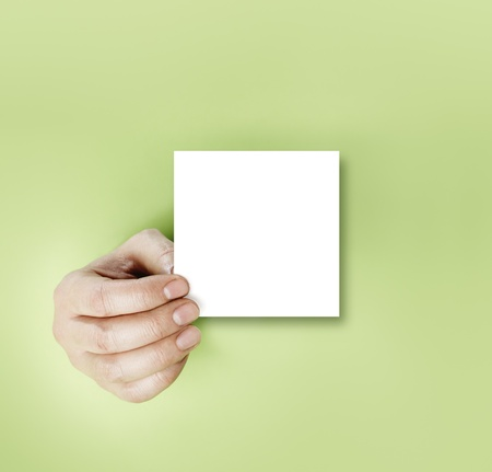 A hand holding a blank note over green background. Stock Photo - 12956071
