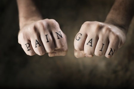 gain: Man with fake tattoos Pain and Gain on his hands, referring to the exercise motto No Pain, No Gain.