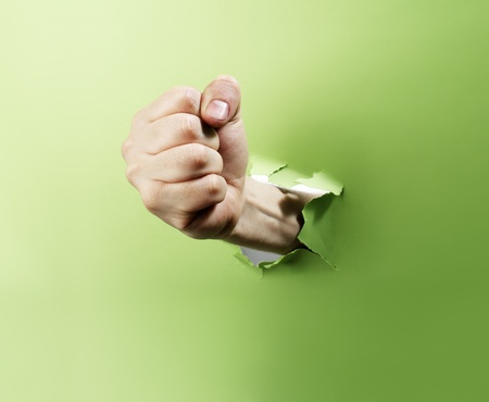 penetration: Man punching through green paper with his fist. Stock Photo
