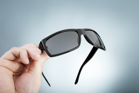 high quality: Man holding a pair of high quality fashion sunglasses in his hand. Stock Photo