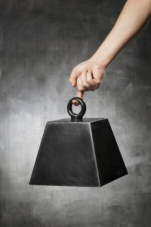 heavy weight: Man hanging a fake prop weight from his finger. Stock Photo