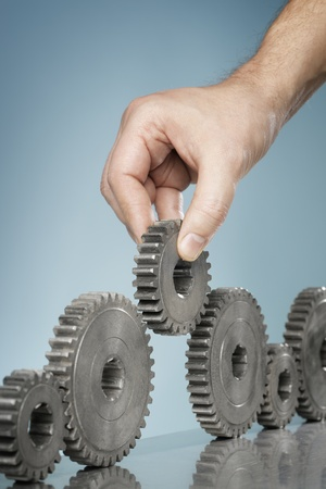 gearwheel: Man adding a cog gear wheel into a row of old cogs. Stock Photo
