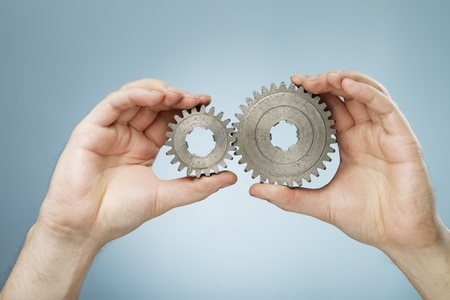 toothed: Man holding two different sizes metallic cog gear wheels in his hands.