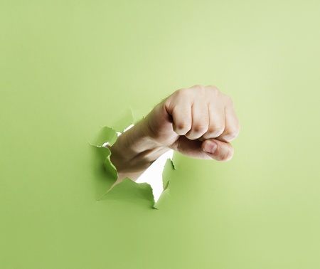 penetration: Man punching through green cardboard with his fist. Stock Photo