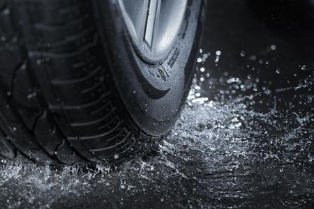 llantas: Neum�ticos de coches chapoteando en el agua. Foto de archivo