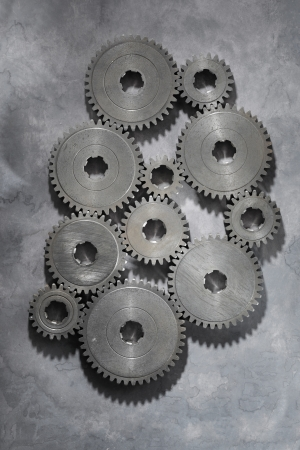 toothed: Old metallic cog gear wheels on grey background.