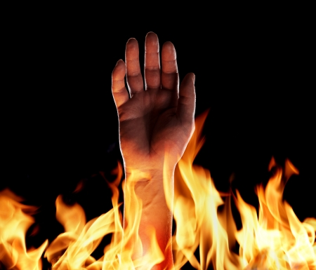 infernal: Hand sticking up from flames. Stock Photo