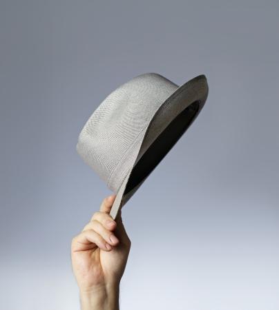 salut: Man tippar hans vintage trilby hatt. Stockfoto