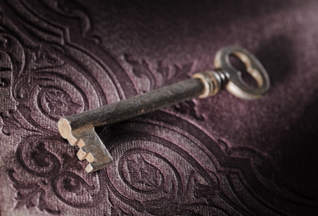 Old key on an ornamental 19th century book cover. Stock Photo - 13885320
