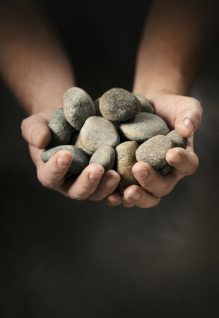 Man holding small rock pebbles in his cupped hands. Stock Photo - 13885323