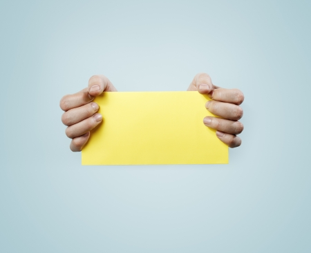Hands holding a yellow card. Stock Photo - 13885327