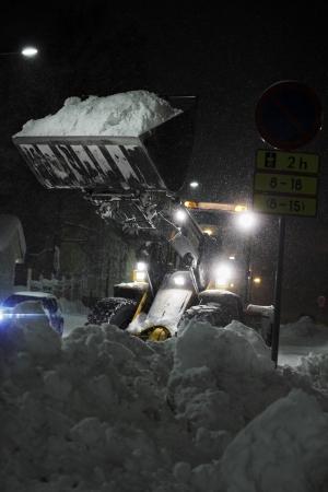 front loader: Un Cargador frontal en tormenta de nieve en Finlandia.