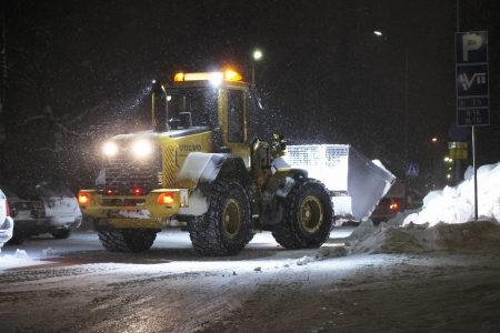 front loader: A Front Loader working in snow storm, Finland. Editorial