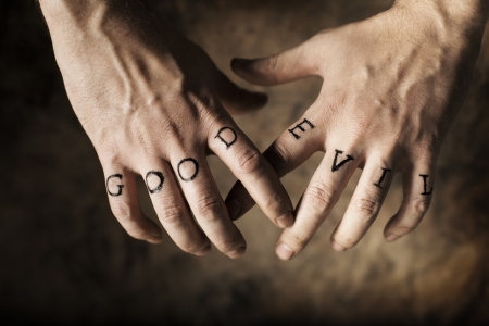duality: Man with Good and Evil (fake) tattoos on his hands.