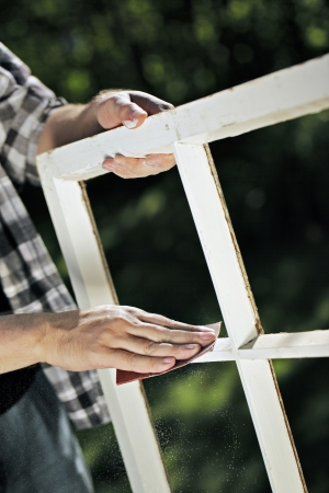 sandpaper: Man using a piece of abrasive sandpaper on an old window frame. Stock Photo