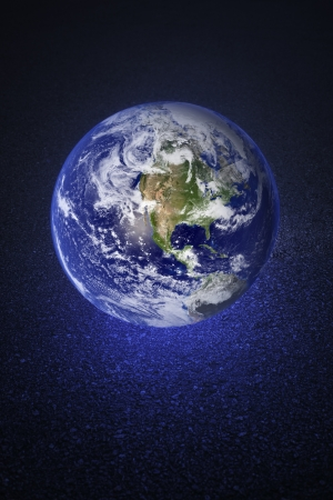 A Glowing earth on asphalt road. Earth image provided by NASA.
