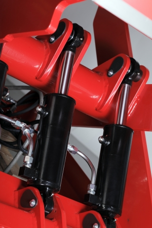 Industrial hydraulic cylinders on red machinery. Stockfoto