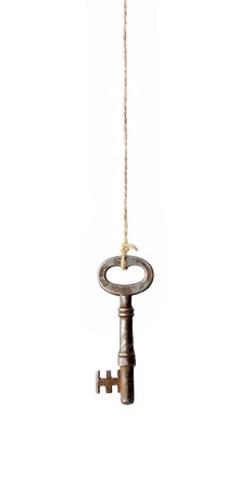 Old antique rusty key hanging from a string.