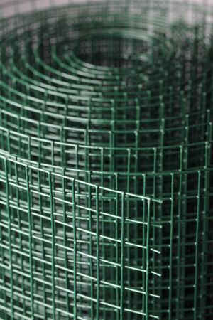 Coated green metallic wire mesh used in gardening by protecting plants from animals. photo