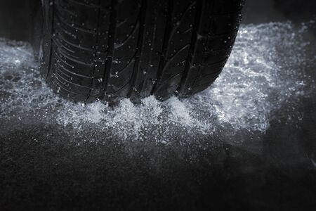 A Car tire on a wet road. The rain groove is a design element of the tread pattern specifically arranged to channel water away from the footprint.