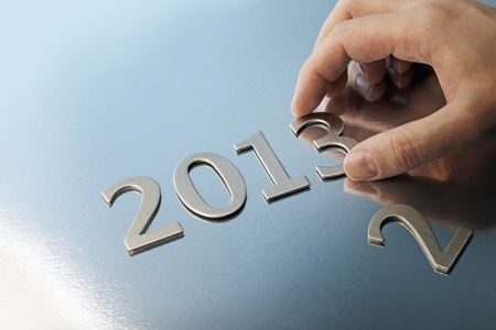 Hand adjusting the year number to 2013. photo
